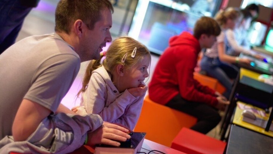 father and girl playing video game National Videogame Museum