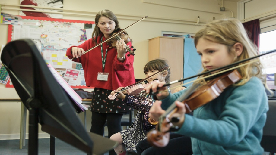 Saffron Centre for Young Musicians - Saffron Walden - Three girls playing violins and reading sheet music