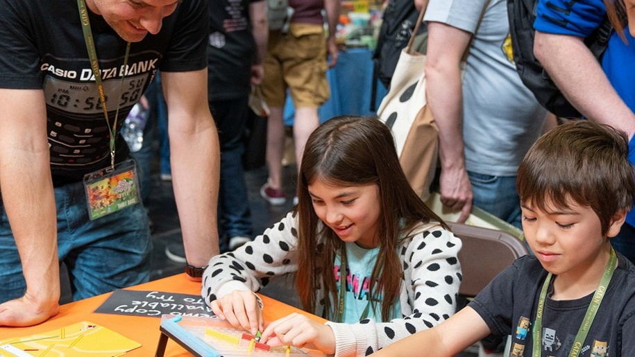boy and girl playing gmae watched by day UK Games Expo