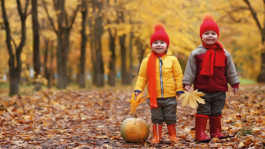 Two young children with pumpkin in autumn woodland